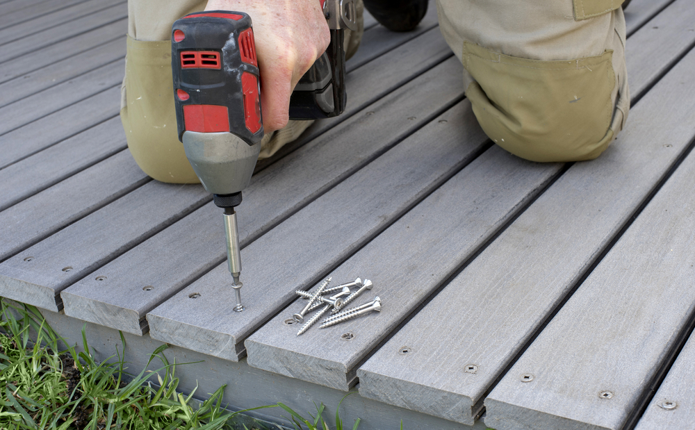 Deck contractor repairing deck boards, deck repair services